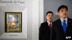 2017年10月13日,被香港媒体认定为前美国中央情报局特工李振成(音译)的男子(打蓝色领带者)站在佳士得香港展厅的保安员前面,身后是达芬奇的画作 。