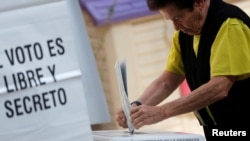 A voter casts a ballot during the election of 60 deputies, to form the Constituent Assembly that will create a constitution for Mexico City, in Mexico City, June 5, 2016.