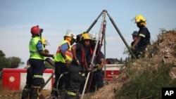 Petugas penyelamat darurat berusaha untuk membebaskan penambang liar yang terjebak di bekas poros tambang emas dekat Benoni, Afrika Selatan, Minggu (16/2).