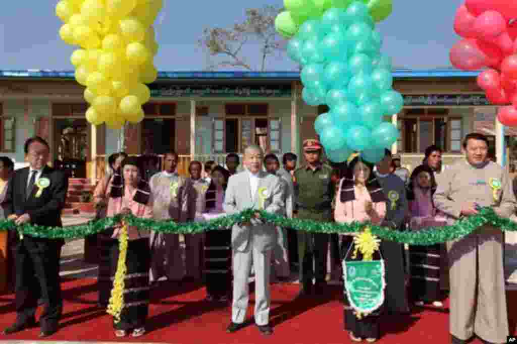 Yohei Sasakawa, centre, Japan Goodwill Ambassador for the Welfare of the National Races in Myanmar, Chairman of the Nippon Foundation, Mikio Numata, left, Japan ambassador to Myanmar, and Sao Aung Myat, right, Shan State chief minister, cut ribbon during