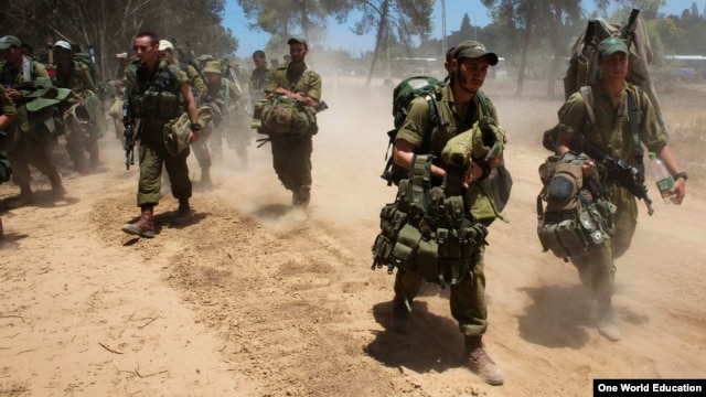 Israeli soldiers walk towards a staging area outside the Gaza Strip, July 18, 2014.