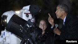 President Barack Obama looks up at the moon as he talks with Agatha Sofia Alvarez-Bareiro, left, a high school senior from the Brooklyn borough of New York, at the second-ever White House Astronomy Night on the South Lawn of the White House in Washington, Oct. 19, 2015.