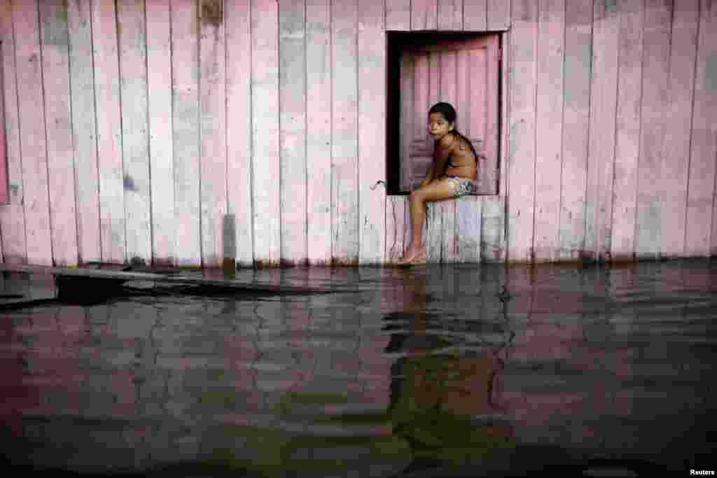 A child is seen on a street flooded by the rising Rio Solimoes, one of the two main branches of the Amazon River, in Anama, Amazonas state, Brazil.
