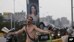 یک تظاهرکننده انجیل به دست و برهنه در مقابل پلیس ضدشورش کاراکاس اعتراض می کند - ۲۰ آوریل ۲۰۱۷