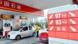 A price board with arrows indicating falling fuel prices is seen as an employee fills the tank of a car at a PetroChina gas station in Hangzhou, Zhejiang province, China, March 26, 2013.