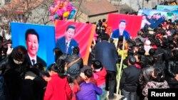 Người dân Trung Quốc cầm hình ảnh của ông Tập trong một dịp đón Tết Nguyên đán.