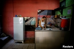 Aridania Rubens works beside a Chinese-made Haier refrigerator at her restaurant in Havana, Feb. 10, 2017.