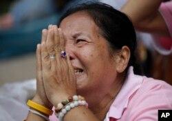 A woman prays for Thailand's King Bhumibol Adulyadej at Siriraj Hospital where the king is being treated in Bangkok, Thailand, Thursday, Oct. 13, 2016.