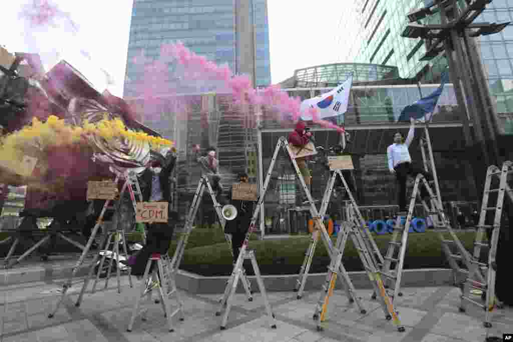 South Korean peace activists on the ladders light smoke bombs during a rally supporting Myanmar's democracy in Seoul.