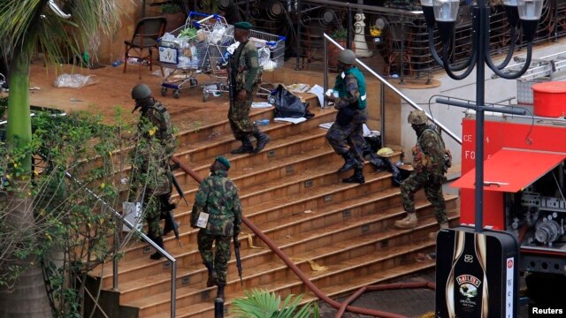 Kenya Defense Forces soldiers move at the main entrance of Westgate shopping centre, on the fourth day since militants stormed into the mall, in Nairobi, Sept. 24, 2013.