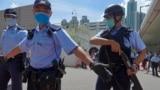 资料照片:当香港首位被控涉嫌违反国安法的唐英杰坐着轮椅被押解至法院时港警戒备。(2020年7月6日)