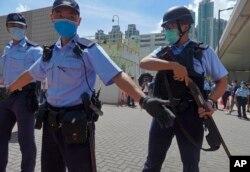 當香港首位被控涉嫌違反國安法的唐英傑坐著輪椅被押解至法院時港警戒備。 (2020年7月6日)