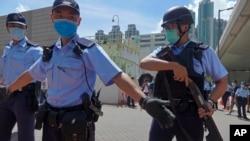 当香港首位被控涉嫌违反国安法的唐英杰坐着轮椅被押解至法院时港警戒备。(2020年7月6日)