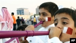 Qatari boys with their faces painted in the colors of their national flag, blow vuvuzelas, celebrating the emirate's selection as the host for the 2022 World Cup, Doha, 02 Dec 2010