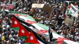 The Muslim Brotherhood's Islamic Action Front supporters carry banners and a large Jordanian flag at the biggest protest in the kingdom since late 2010, in Amman, Jordan, Friday, Oct. 5, 2012. (AP)
