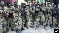 Пророссийские активисты позируют после захвата отделения милиции в Славянске 13 апреля 2014