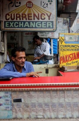 A currency exchanger waits for customers in New Delhi, June 13, 2013.