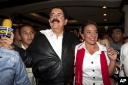 FILE - Free Party presidential candidate Xiomara Castro, right, and her husband, ousted President Manuel Zelaya, leave after giving a press conference before partial election results were announced in Tegucigalpa, Honduras, Nov. 24, 2013.
