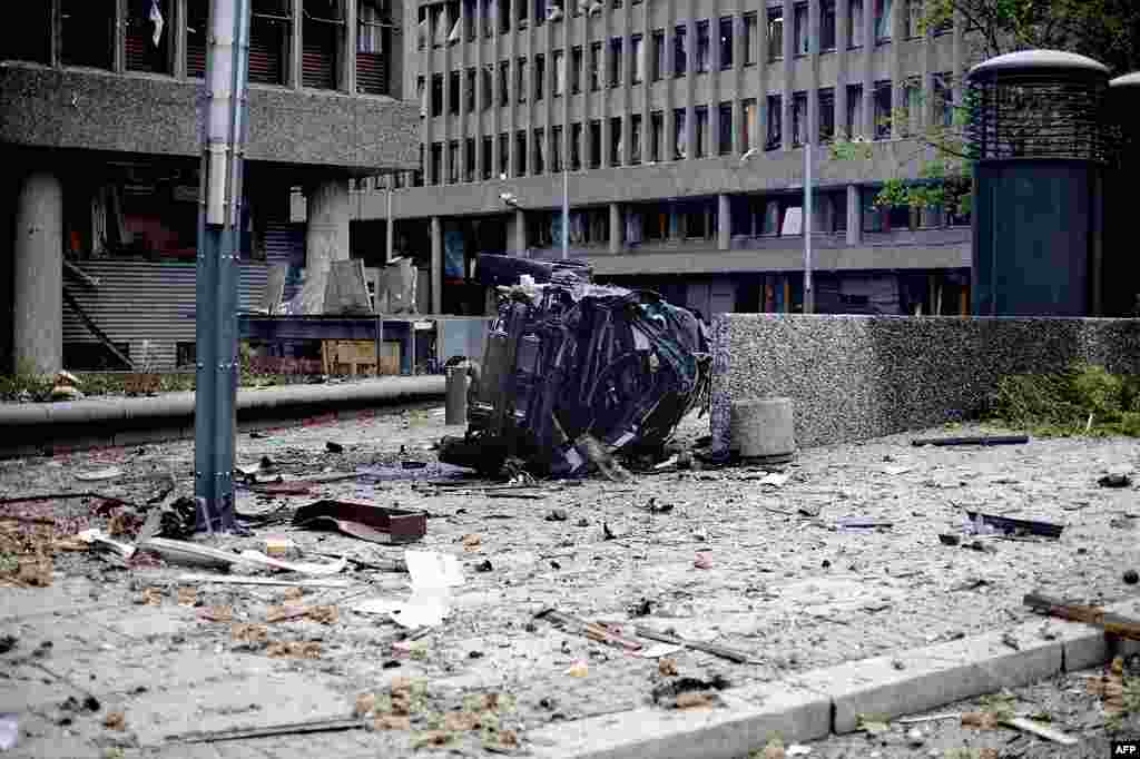 The wreckage of a car lies outside government buildings in the center of Oslo, Friday July 22, 2011, following an explosion that tore open several buildings including the prime minister's office, shattering windows and covering the street with documents.