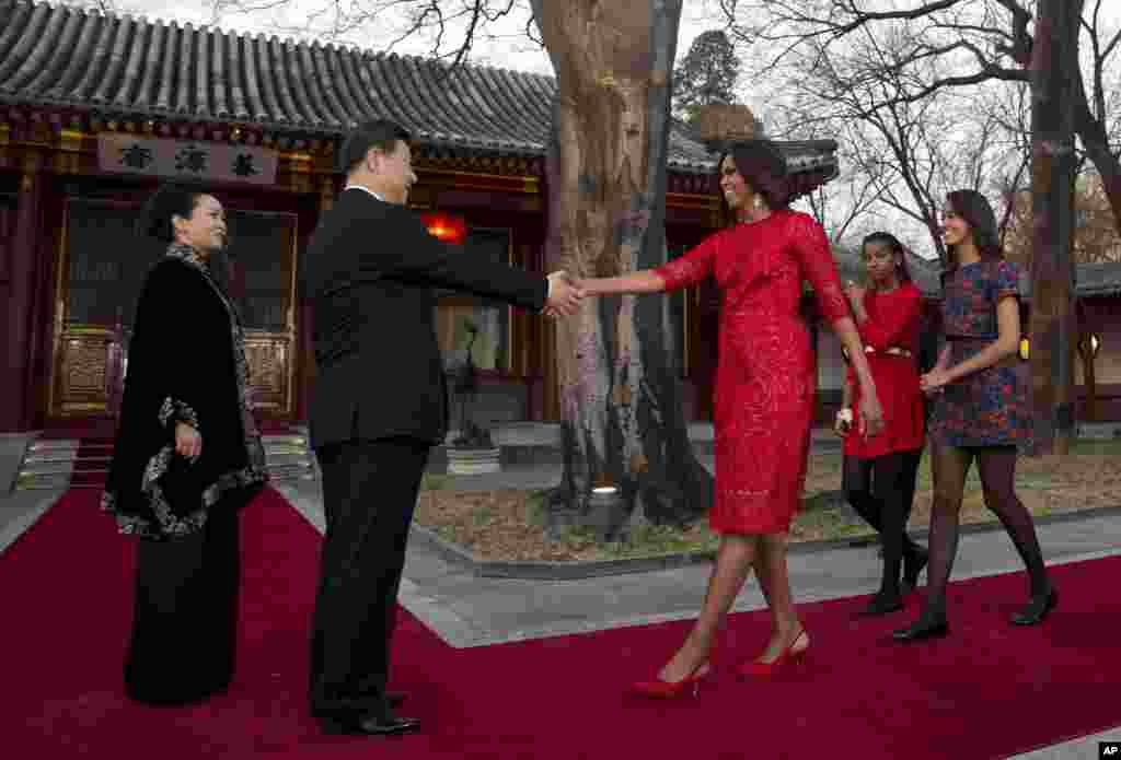 U.S. first lady Michelle Obama, followed by her daughters Malia and Sasha, is greeted by Chinese President Xi Jinping and his wife Peng Liyuan at the Diaoyutai State guest house in Beijing, March 21, 2014.