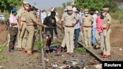 Petugas polisi memeriksa jalur kereta api setelah kereta menabrak pekerja migran yang tidur di lintasan di distrik Aurangabad di negara bagian barat Maharashtra, India, 8 Mei 2020. (Foto: Reuters)