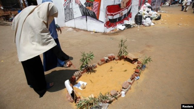 Members of the Muslim Brotherhood and supporters of ousted Egyptian President Mohamed Morsi walk near the mock grave of a protester who was killed yesterday during clashes around Cairo University and Nahdet Misr Square in Giza, Cairo, Egypt, July 23, 2013.