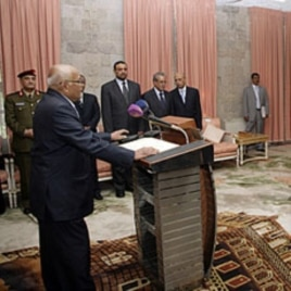 Yemen's newly appointed Prime Minister Mohammed Salem Basindwa (front L) takes the oath of office at the Republican Palace in Sana'a, December 10, 2011.