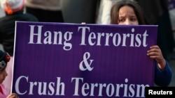 . Một em bé cầm tấm bảng với hàng chữ 'Treo cổ kẻ khủng bố, Tiêu diệt chủ nghĩa khủng bố' trong cuộc biểu tình ở Lahore, lên án vụ các tay súng Taliban tấn công một trường học ở Peshawar, giết chết học sinh và nhân viên nhà trường 21/12/14