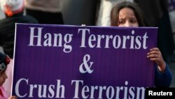 A supporter of political party Pakistan Awami Tehreek (PAT), holds a sign with others condemning an attack by Taliban gunmen on the Army Public School in Peshawar, during a rally in Lahore, Dec. 21, 2014.