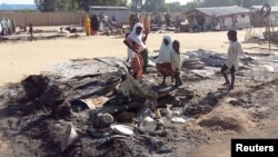 FILE - People stand amid the damage at a camp for displaced people after an attack by suspected Boko Haram insurgents in Dalori, Nigeria, Nov. 1, 2018.