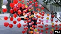 """Seorang penjaja balon menjual balon-balon berbentuk """"hati"""" atau cinta menjelang Valentine's Day di Lahore, Pakistan (foto: ilustrasi)."""