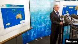 John Young, general manager of the emergency response division of the Australian Maritime Safety Authority (AMSA), answers a question as he stands in front of a diagram showing the search area for Malaysia Airlines Flight MH370 in the southern Indian Ocea