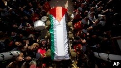 Members of the Palestinian national security forces carry the body of Palestinian Cabinet member Ziad Abu Ain during his funeral in the West Bank city of Ramallah, Dec. 11, 2014.