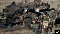 Separatis pro-Rusia berjalan di dekat tank pasukan Ukraina yang mereka hancurkan di desa Lohvynove, pinggiran Debaltseve, Ukraina timur (22/2).