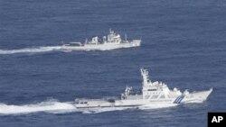 Корабль Береговой охраны Японии и китайский рыболовный патрульный корабль (на заднем плане) в акватории спорных островов. 18 сентября 2012 г.