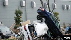 Bangkai mobil tumpang tindih di Sendai, Miyagi, Jepang, Senin (14/3).