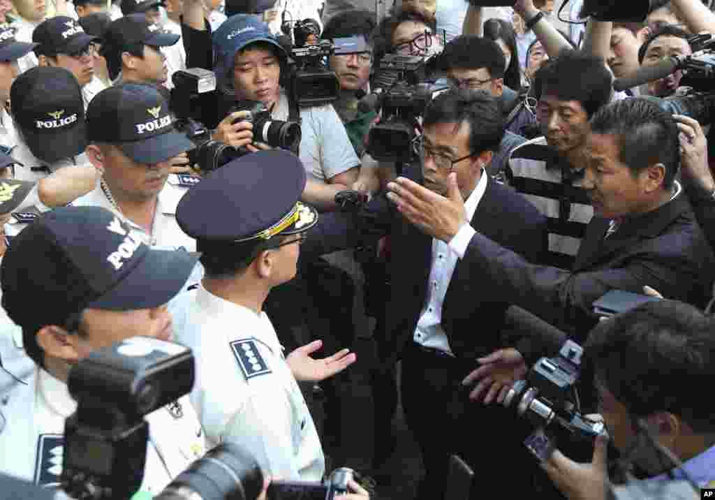 Para anggota keluarga penumpang kapal kapal feri Sewol yang tenggelam meminta pada polisi untuk bertemu awak kapal usai sidang pra-peradilan untuk mereka di Pengadilan Distrik Gwangju, Gwangju, Korea Selatan (10/6).(AP/Ahn Young-joon)