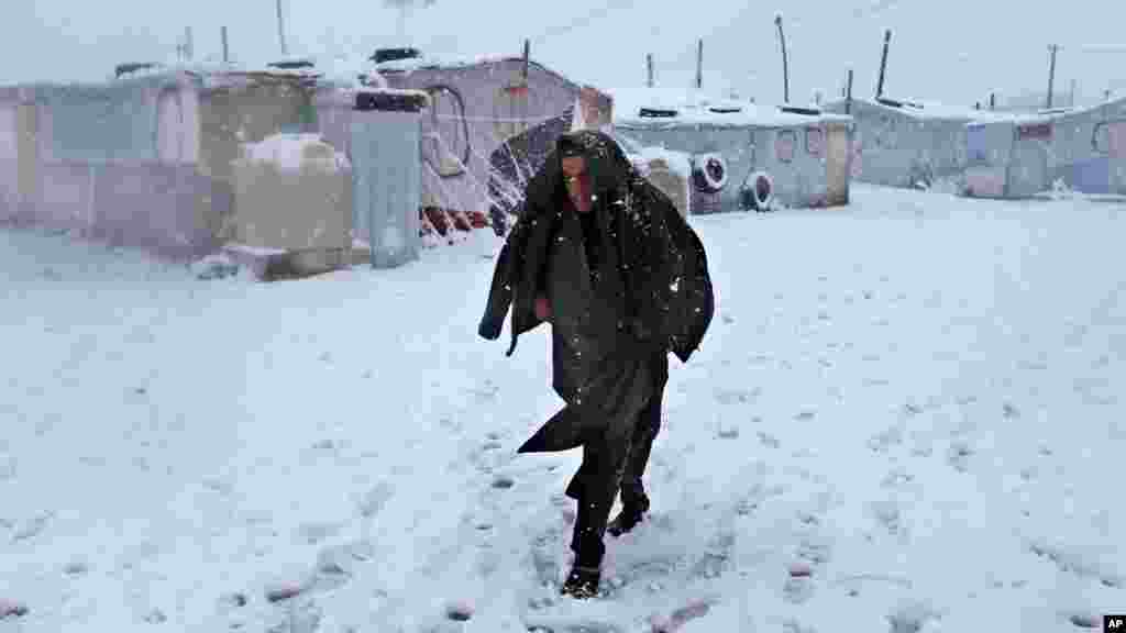 A Syrian man walks in the snow at a refugee camp in Deir Zannoun village, in the Bekaa valley, east Lebanon, Jan. 7, 2015.