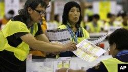 Pera petugas pemilu melakukan perhitungan kartu suara dalam pemilu parlemen di Hong Kong (10/9).