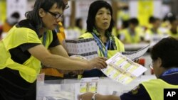 Electoral officers count ballots at the central ballot counting station after legislative elections in Hong Kong, Monday, Sept. 10, 2012.