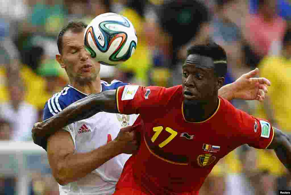 Russia's Sergey Ignashevich fights for the ball with Belgium's Divock Origi during their match at the Maracana stadium in Rio de Janeiro, June 22, 2014.