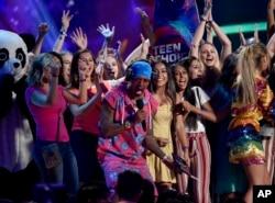 Nick Cannon (tengah) menganugerahkan penghargaan Fandom Choice di acara Teen Choice Awards 2018 kepada ARMY, komunitas penggemar boyband K-Pop BTS (Foto: Chris Pizzello/Invision/AP) .