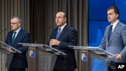 Turkey's EU Affairs Minister Omer Celik, right, Foreign Minister Mevlut Cavusoglu, center, and Finance Minister Agbal Nihat address the media after an EU Turkey Accession Intergovernmental Conference at the EU Council building in Brussels, June 30, 2016.