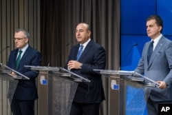 FILE - Turkey's EU Affairs Minister Omer Celik, right, Foreign Minister Mevlut Cavusoglu, center, and Finance Minister Agbal Nihat address the media after an EU Turkey Accession Intergovernmental Conference at the EU Council building in Brussels, June 30, 2016.