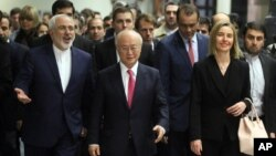 Iranian Foreign Minister Mohammad Javad Zarif, left, Director General of the International Atomic Energy Agency, IAEA, Yukiya Amano of Japan and European Union High Representative Federica Mogherini, right, arrive at the International Atomic Energy Agency
