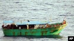 Para migran berada di dalam perahu menunggu bantuan dari Angkatan Laut Italia di perairan Capo Passero, Sisilia, Italia, 27 Maret 2013 (Foto: dok).
