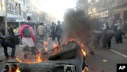 Iranian anti-government protesters set a garbage can on fire, in Tehran, Iran, February 14, 2011
