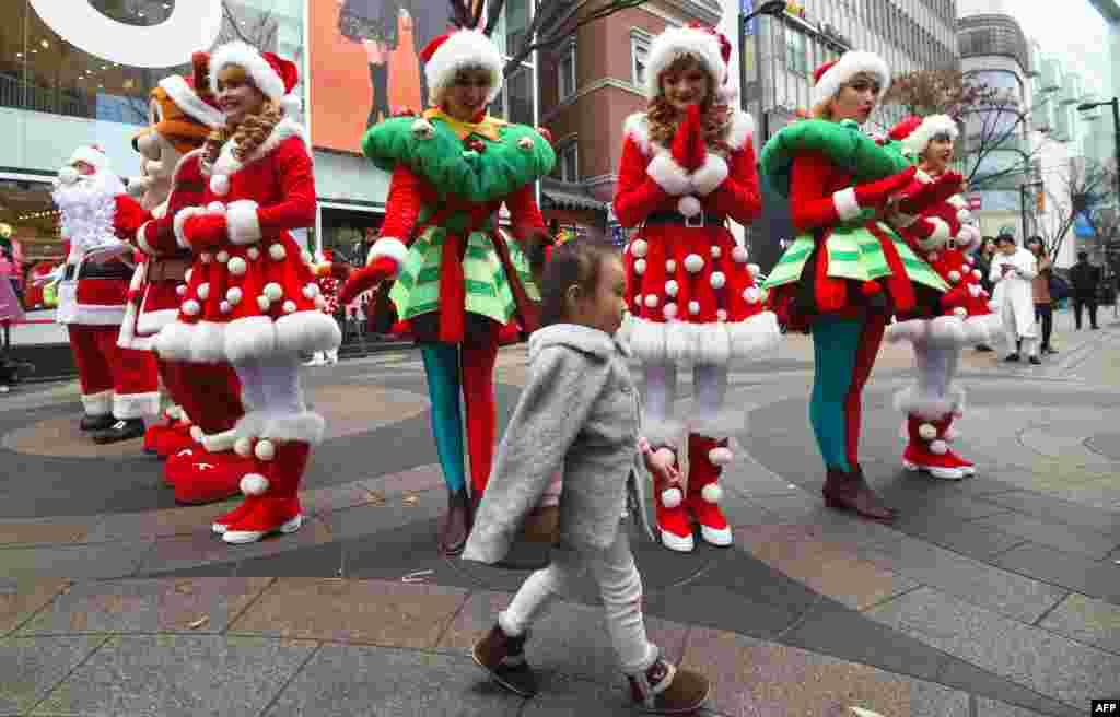 ក្មេងស្រីម្នាក់ដើរនៅពីមុខអ្នកសម្តែងនៅក្នុងឈុតតា Santa Claus ក្នុងព្រឹត្តិការណ៍តាមផ្លូវមួយដើម្បីផ្សព្វផ្សាយពីរដូវបុណ្យណូអែល នៅក្នុងតំបន់លក់ទំនិញមួយនៅក្នុងក្រុងសេអ៊ូល ប្រទេសកូរ៉េខាងត្បូង។