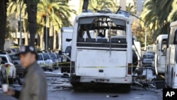 FILE - A man walks past the bus that exploded Tuesday in Tunis.