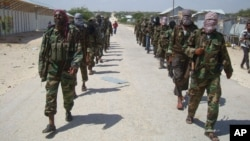 FILE - Members of Somalia's al- Shabab militant group march on the outskirts of Mogadishu, Somalia, March, 5, 2012. on Thursday, heavily armed al-Shabab extremists stormed a military base in Somalia's semiautonomous state of Puntland, killing close to 70 people and wounding dozens more.